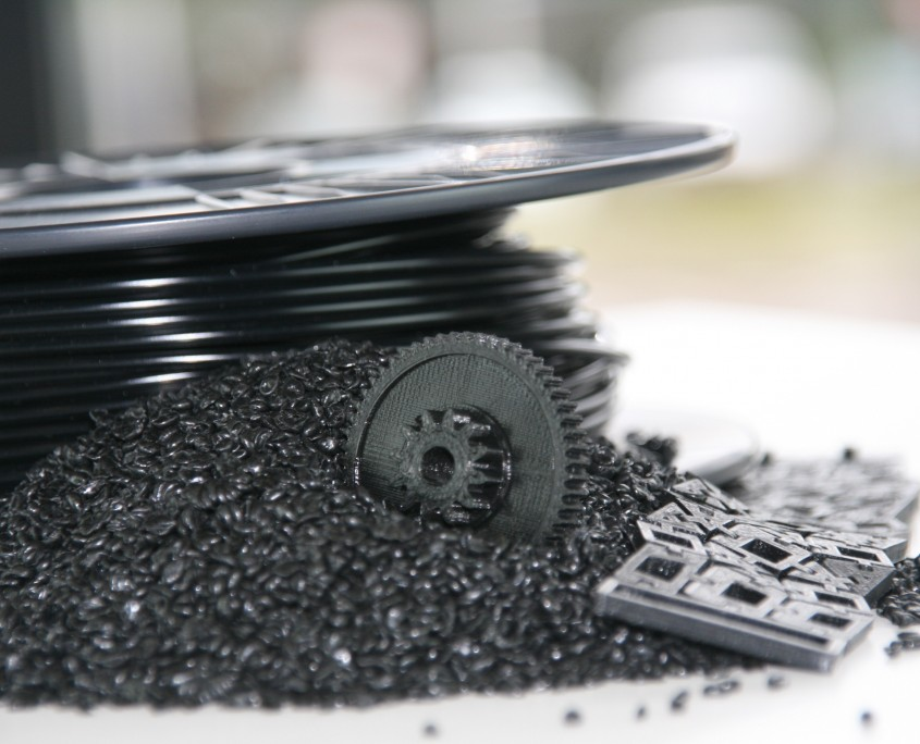 A sample output spool of filament produced by the 3devo 3D printer filament extruder. And some plastic pellets