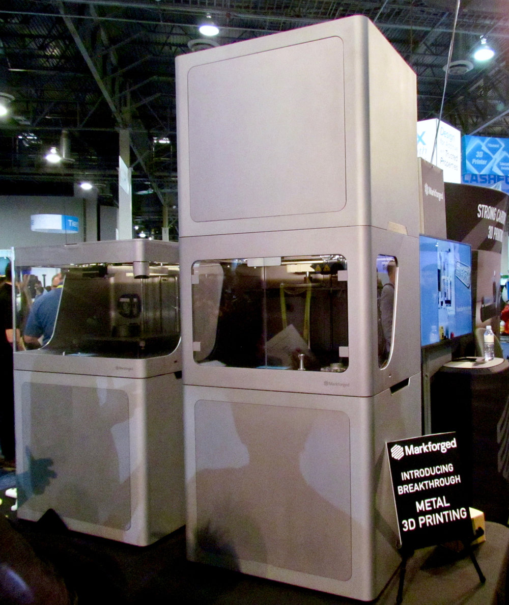 The Markforged Metal X (on the right) 3D metal printer, beside one of its non-metal siblings