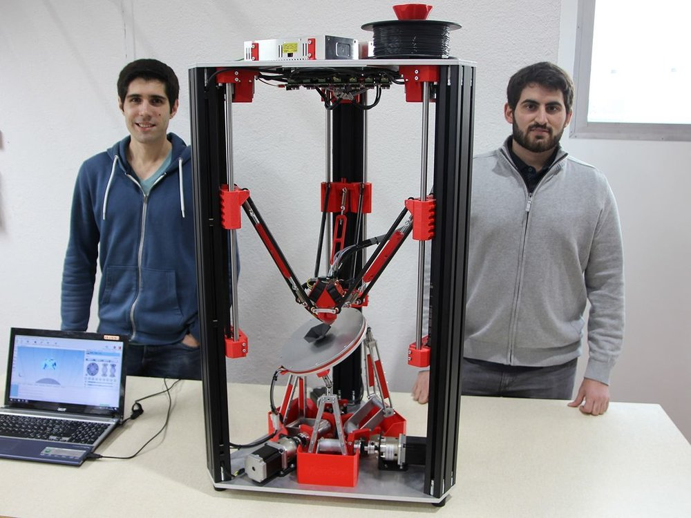 "Oliver Tolar and Denis Herrmann with their ""tilt-bed"" 3D printer"