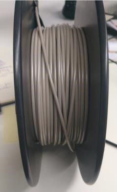 A spool of PEEK plastic filament produced by 3devo