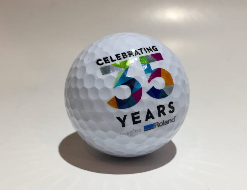 A golf ball with curved surface showing precise color prints by Roland