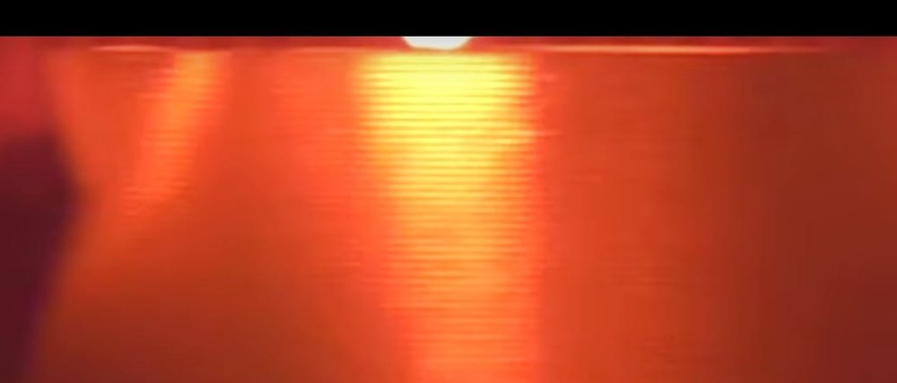 Still from one of MICRON3DP's videos just barely showing a hint of the extruder at the top where the view is cut off