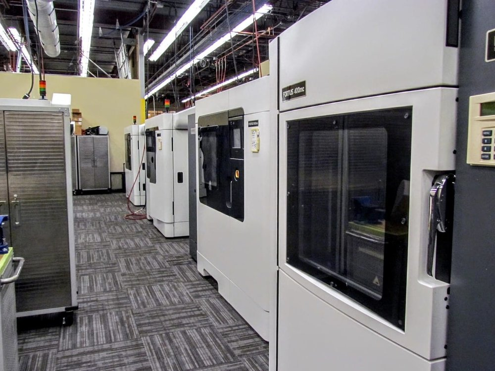 A row of production Stratasys Fortus 3D printers