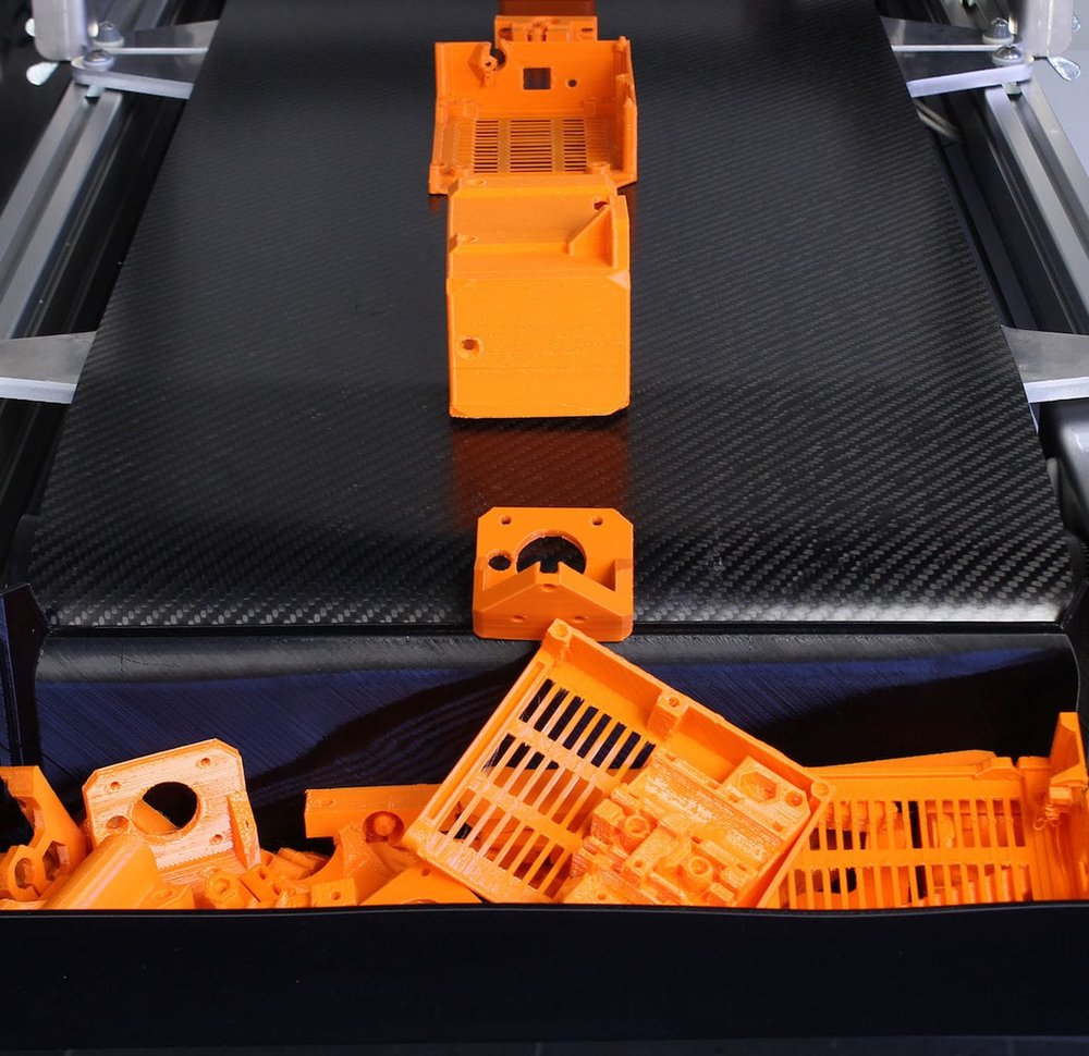 The Blackbelt 3D printer continuously producing 3D printed objects - and dropping them in a bin