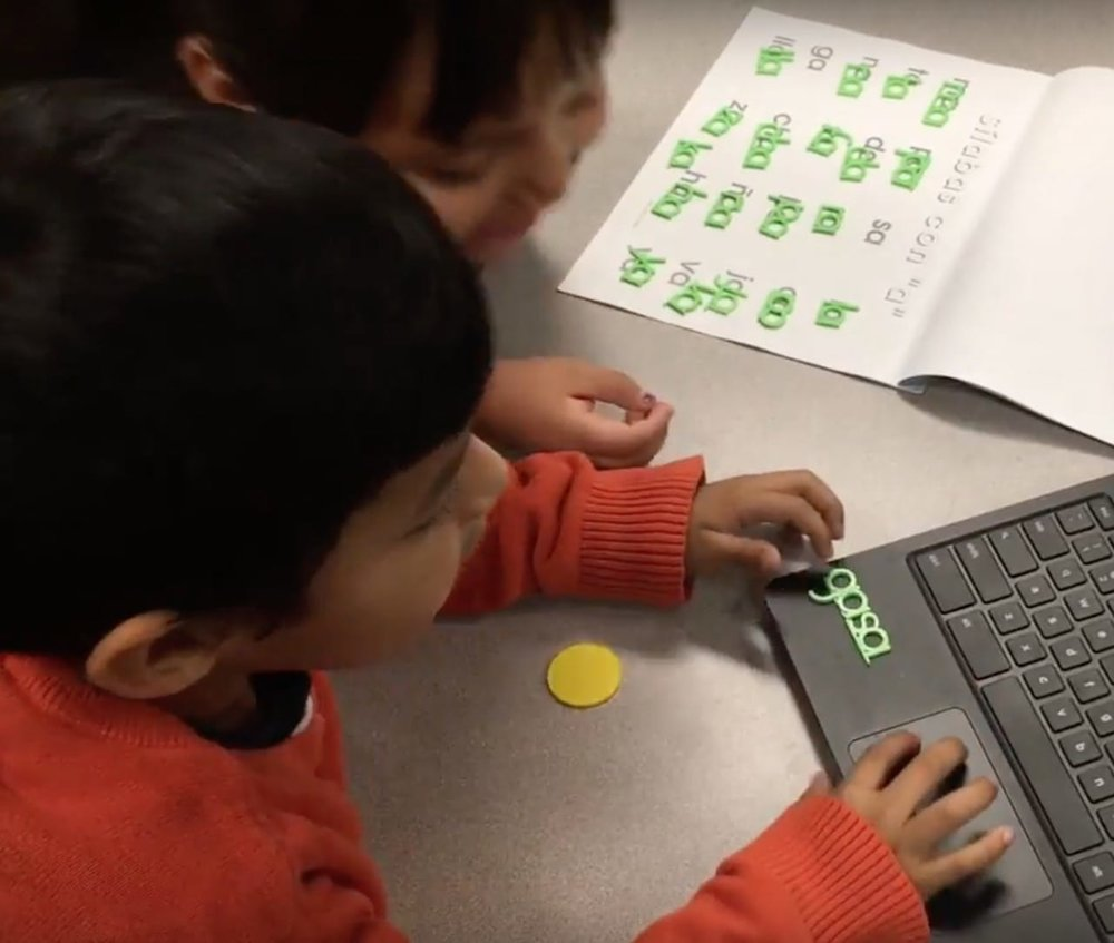 Students working with a 3D printed language tool