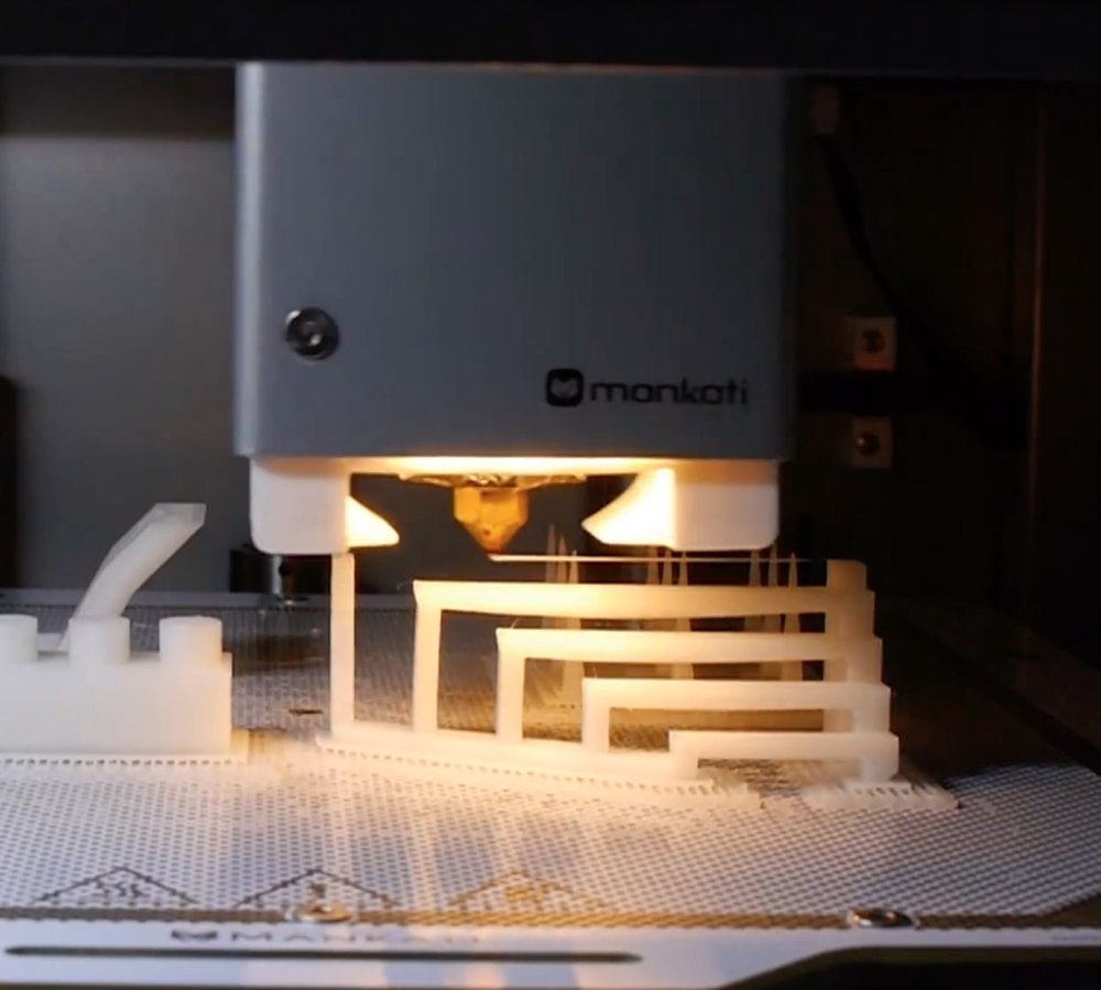 Check out the hot end nozzle, where it is successfully printing a rather long bridge structure