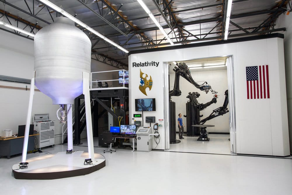 "Relativity Space's 3D rocket printer, with ""sample print"" on the left"