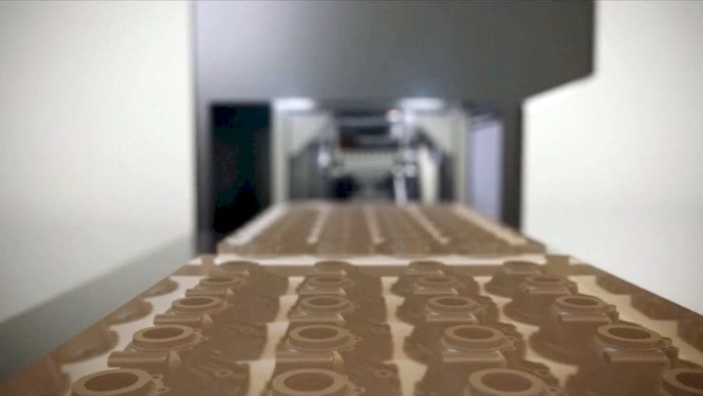 STEP 3D printing production involves a moving conveyor belt to deliver completed prints