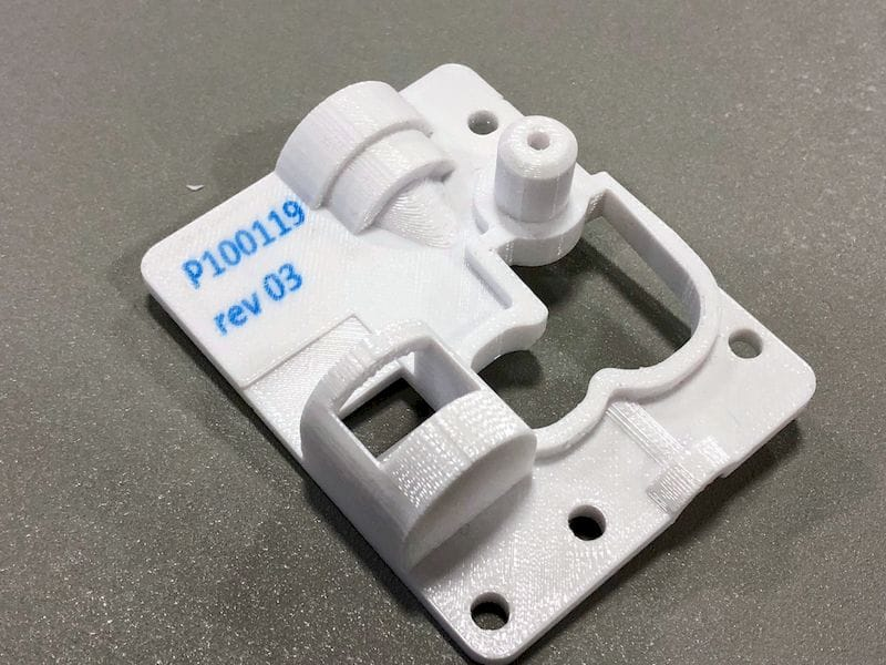 A part 3D printed by Rize with automatically embedded part and version numbers