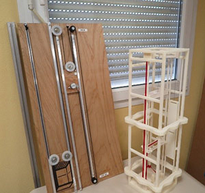 SODIMAS' 3D printed elevator model (right) next to their original wood-mounted mechanical model (left) [Source:  Stratasys ]