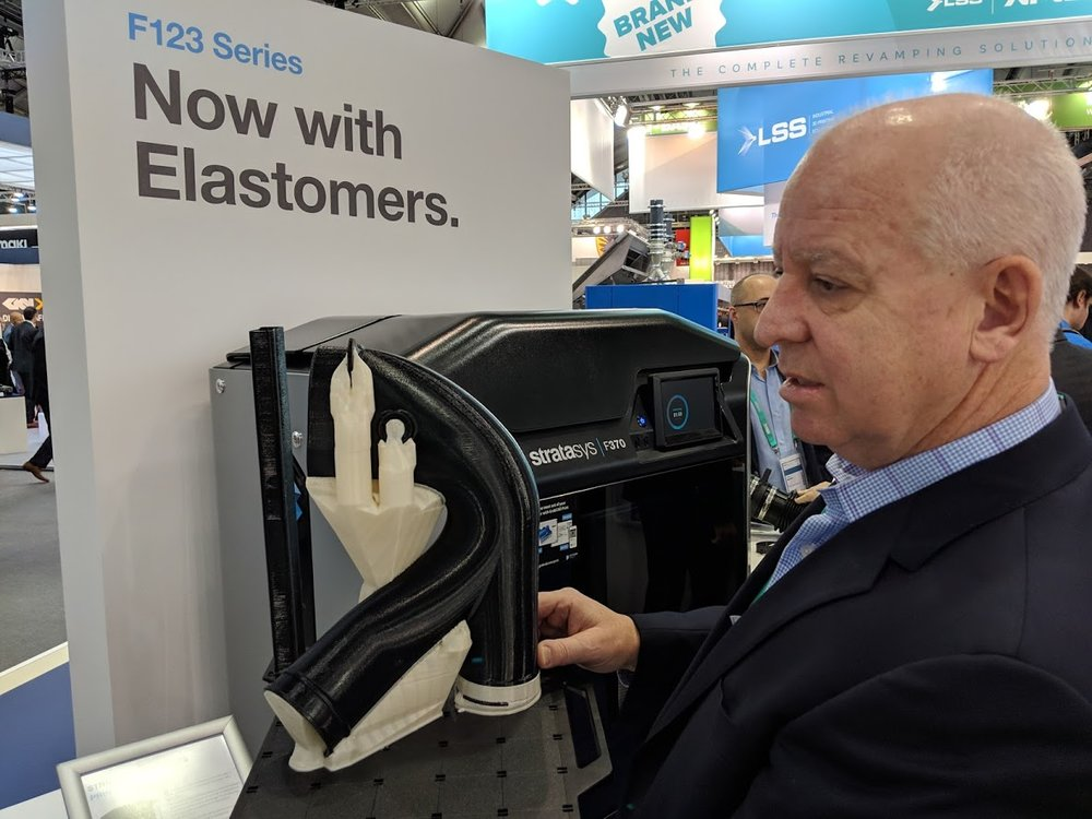 Pat Carey shows off an automotive component 3D printed in new elastomer material, with soluble supports still attached [Image: Fabbaloo]