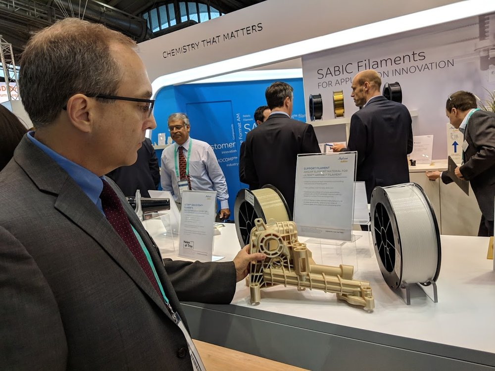Keith Cox, Senior Business Manager, Additive Manufacturing, SABIC looks at a part 3D printed in ULTEM and made using the new breakaway support material at formnext 2018 [Image: Fabbaloo]