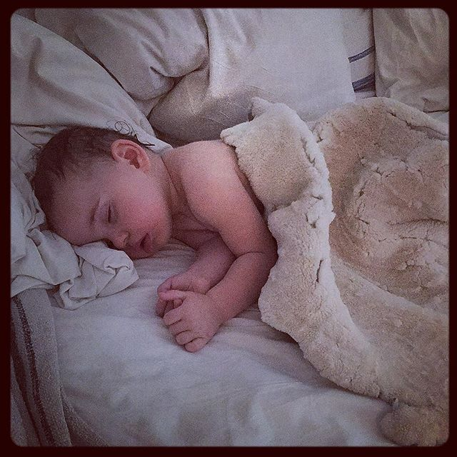 After a hot bath, covered in sheepskins lulu falls asleep for a late afternoon cozy #nap #happybabypose