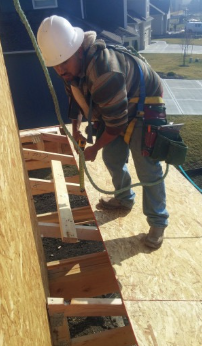 A framing carpenter wears a safety harness secured to a point above him while working on the roof. He is wearing a hardhat and shoes that have good traction for the slope of the roof.    Courtesy builderonline.com