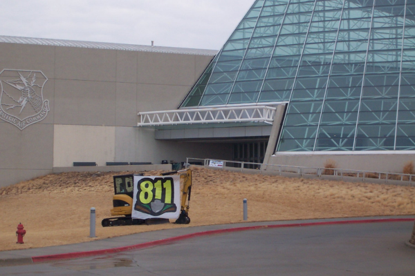 A mini-excavator machine provided by NMC Cat displays an 811 sign at the entrance to the Strategic Air and Space Museum on the day of the Excavation Safety Summit - March 7, 2014
