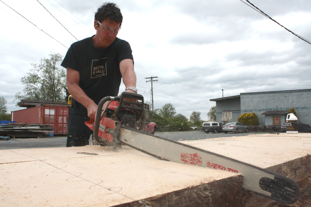 Andrew Vallee carefully cuts one of the spruce slabs that will be made into the Sealaska Corp. Conference Table.