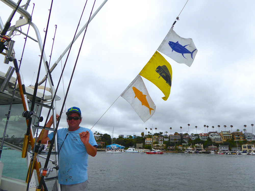 Bongo II with deck hand Marty and Capt Joe putting up the fish flags.