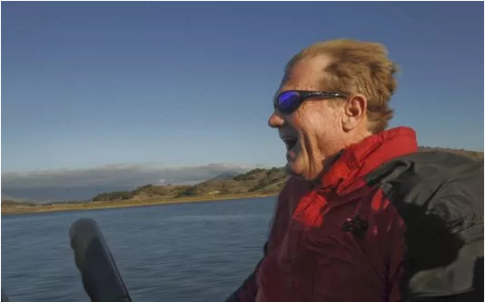 In better times, fishing guide Doug Carlson enjoys the ride as he heads back to the dock at Lake Casitas. Carlson is fighting pancreatic cancer.