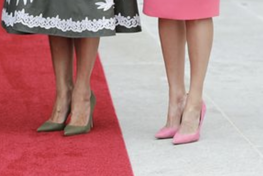 Melania Trump's feet, left. Queen Letizia of Spain's feet, on the right. Both pairs of feet look ugly, over-raised by stiletto heels, and over-pinched by unattractive points. This is a cropped screenshot of a photo by Getty Images.