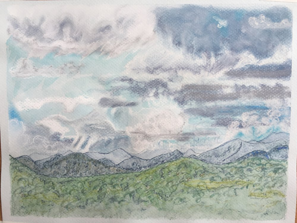 A Changing View: when I started working on this, the clouds were less grey on their undersides, and less plainly rain-laden. So this picture shows, from left to right, the view of the sky as it changed before my eyes. The mountains were outlined first but coloured last. The only pastels are in the sky.