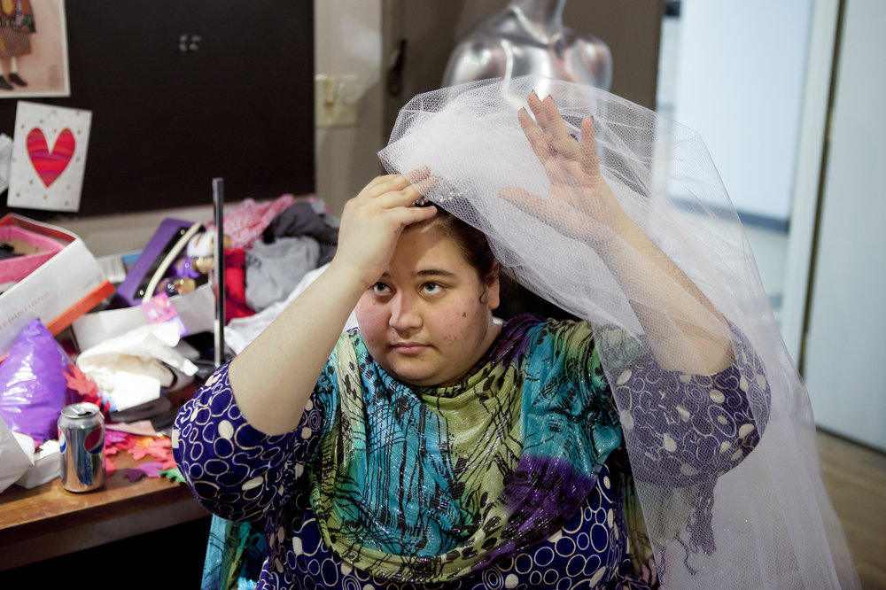 Hafsa tries on a veil that will be used on a mannequin for window displays at Tower City Mall that her stepmom Amie Gilroy designs.