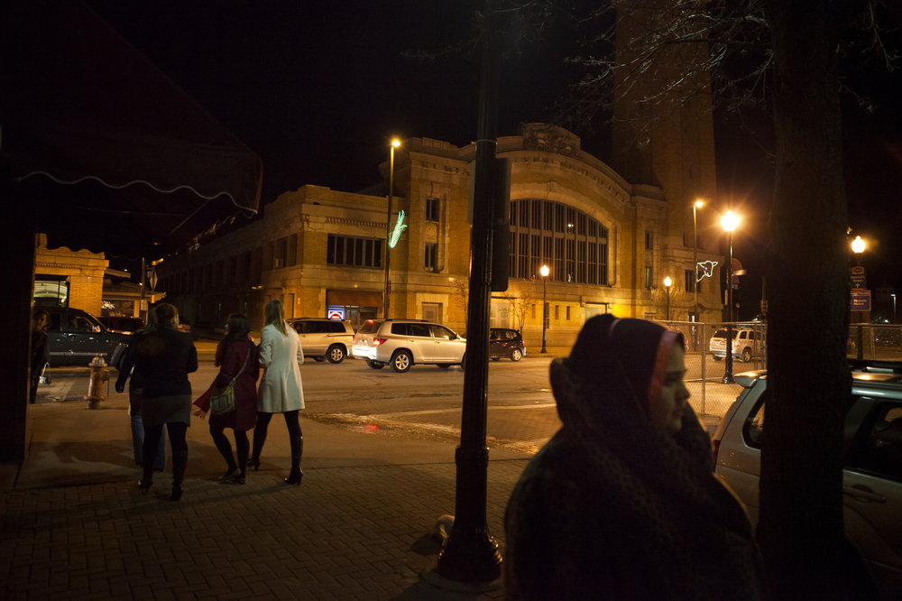 "Hafsa walks past Cleveland's West Side Market. The waves of immigrants to the Cleveland area have shaped the market in many ways. A sign written in Arabic hangs from one stand declaring that, ""Halal meat is sold here."" The stand began to sell halal meat nearly 30 years ago in response to the growing demand of Muslim clients at the market."