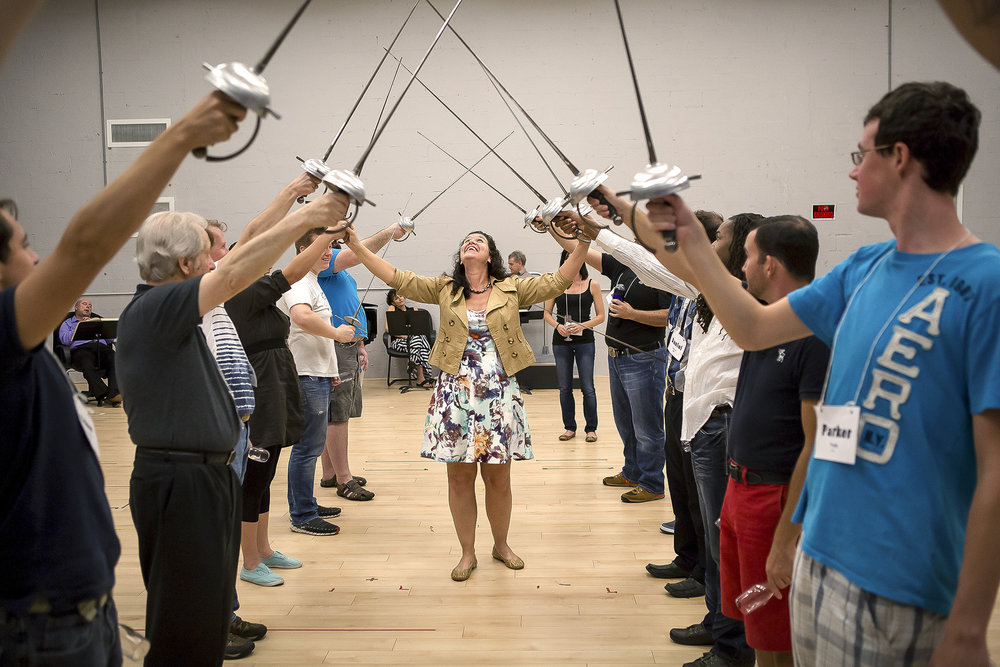 "Director Fenlon Lamb adjusts the way the chorus members hold their swords. ""There is always that moment when you wonder how it will all work out with all the different performers and elements,"" Lamb says."