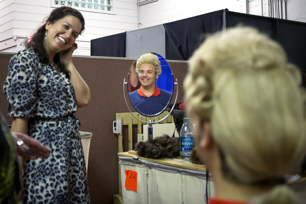 Director Fenlon Lamb smiles as David Portillo, who sings the role of Count Almaviva, tries on a wig. Each wig is handmade and then fitted to suit the individual singers.