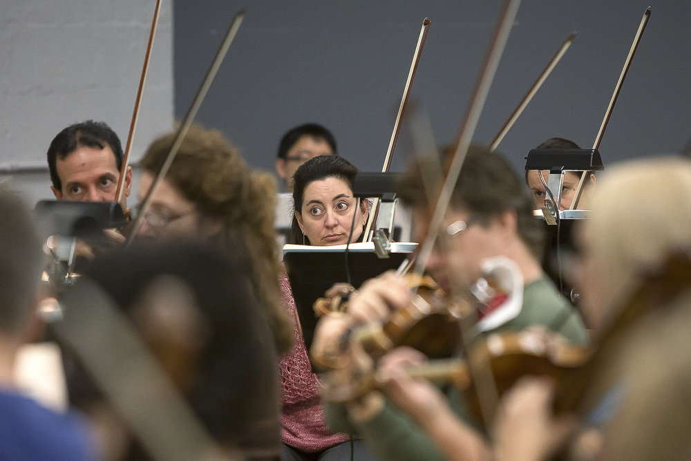 Tina Raimondi watches the conductor as she plays her violin with the orchestra for The Barber of Seville. During the rehearsal with the full orchestra, which is known as the sitzprobe, the opera singers stand in the back and practice their parts with the music as it will be played during the final performances.