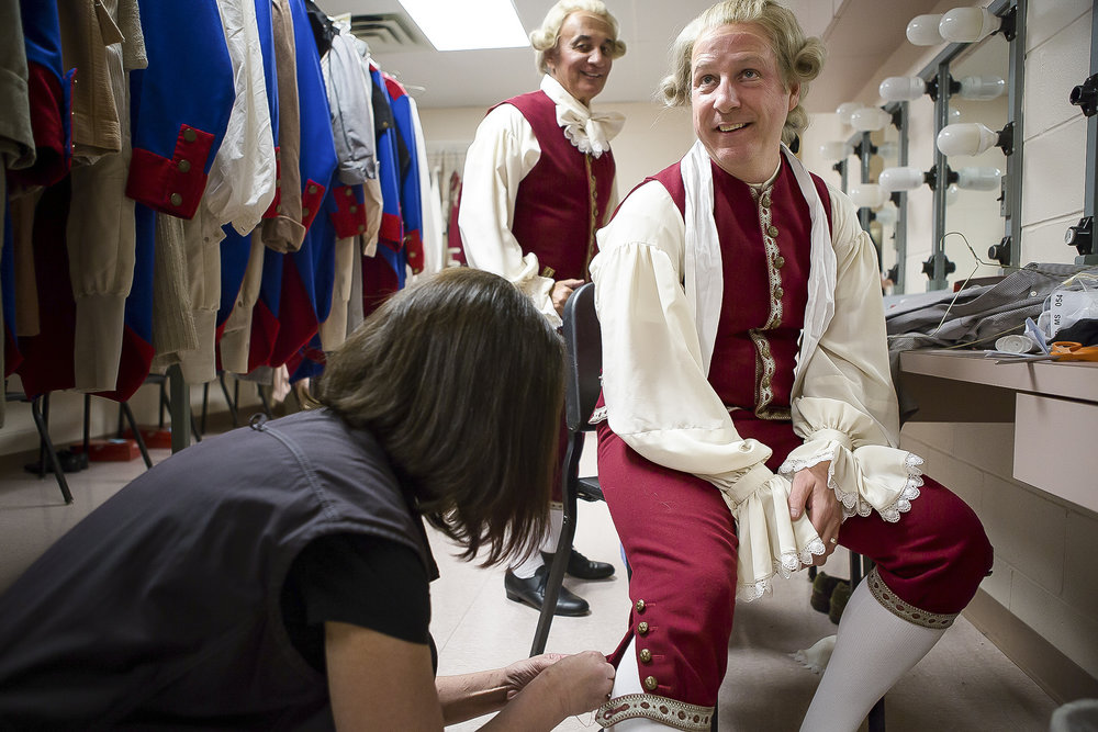 Karen Newhart sews a button on the pants of Joe Cremona, the Palm Beach Opera's accountant-turned-performer, during dress rehearsal. Cremona is a super in the production which means that he has a role onstage but does not sing.