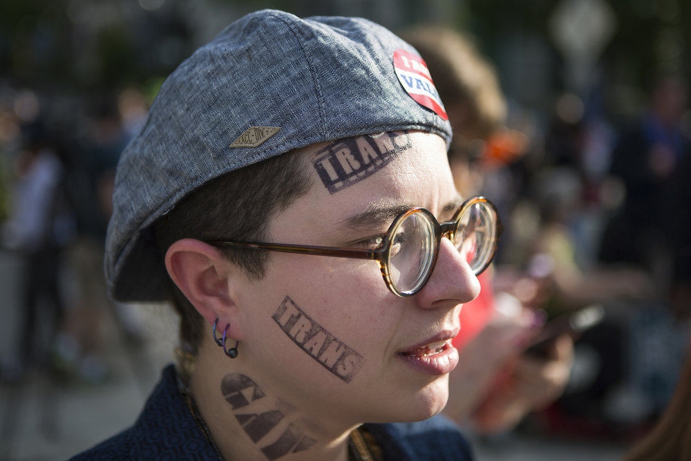 Calvin Dean has their face stamped with different labels as part of a political art project during House Bill 2 protest. House Bill 2 requires people to use the bathroom of the gender on their birth certificate rather than the gender they identify as.