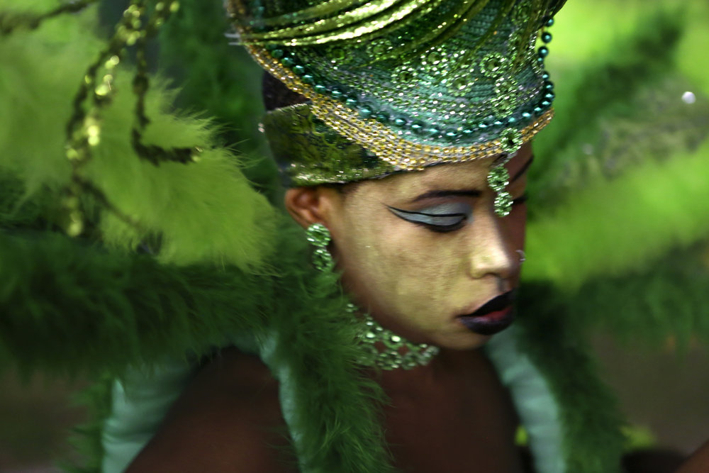 A dancer prepares for the queen costume competition of the Miami Broward One Carnival. Designer Malcolm McSimon, creates elaborate, traditional costumes by hand in a makeshift studio behind his house.