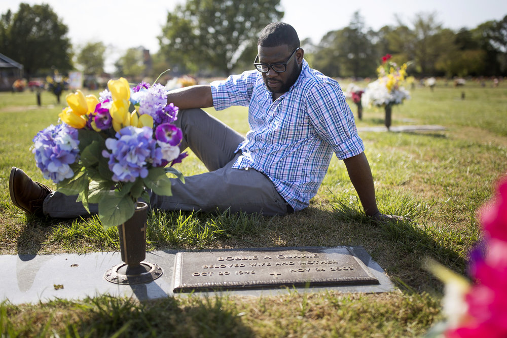 Daeqwon Currie, a recovered heroin addict, sits beside his grandmother's grave where he goes to seek solace in his hometown of Wilson. Daeqwon is building a new foundation working at Dunkin Donuts and regularly attending Farmington Heights Church of God as he continues to stay clean.