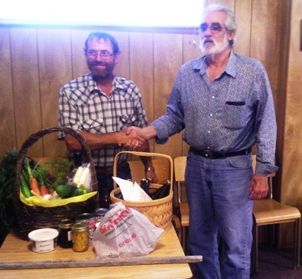 Current Chair  Charles Robinson presents long serving past chair Cliff Maclean on right with a gift basket from council members.