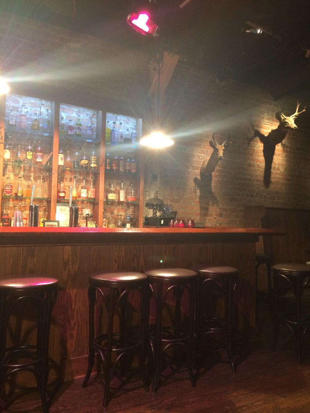 """The """"Speakeasy"""" set, where bottles are filled with colored water due to regulations around serving alcohol in conjunction with nudity. However, according to our guide, the actors have monthly """"employee appreciation parties"""" where they bring in real booze."""