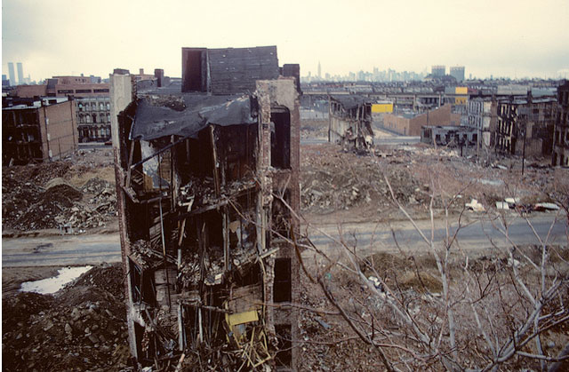 Bushwick, Brooklyn, in 1982 as photographed by Steven Siegel.  The World Trade Center towers are visible in the distance on the extreme left.  Courtesy The Gothamist.