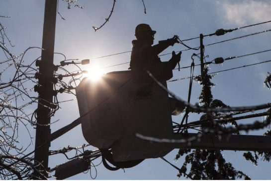 A linesman repairing damage following the Christmas ice storm in the Toronto area.  Courtesy The Toronto Star.