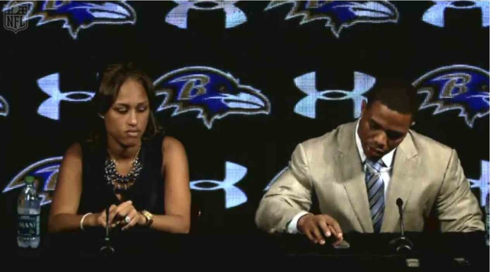 "Baltimore Ravens running back Ray Rice checking notes on his smartphone during an ""apology"" press conference.  At left is his wife, Janay Palmer.   Image from nfl.com."