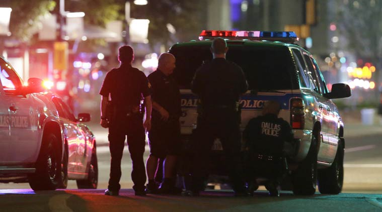 Police take cover behind a vehicle outside a parking garage in downtown Dallas early Friday, July 8, 2016. (AP Photo)