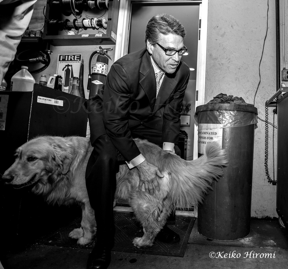 Former Texas Gov. Rick Perry plays with Chester, Golden retriever at Weed Automotive in Concord, N.H on March 12, 2015.