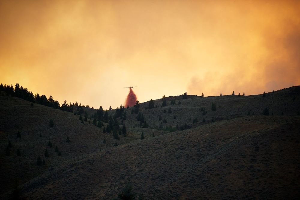 A fire retardant bomber unleashes and heads to the west. Beaver Creek Fire, Idaho.