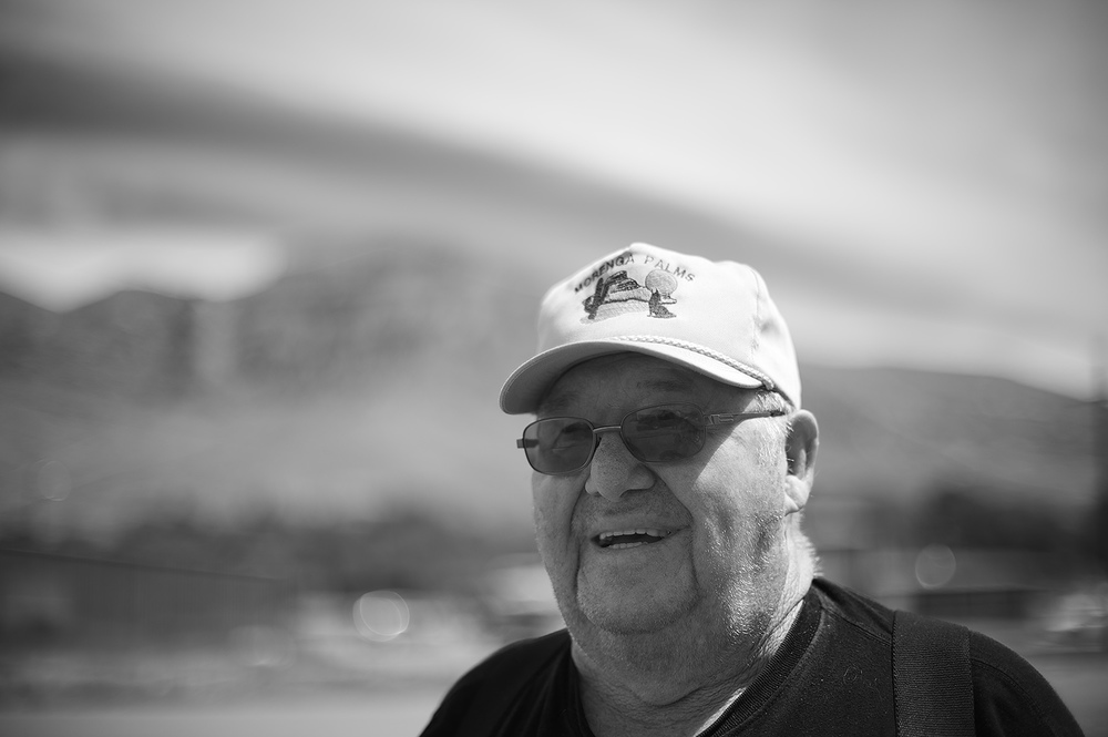 "John, a lifetime resident of Arco, Idaho poses for a portrait. In the background is the infamous hill showcasing, in large painted white numbers, the graduating classes of nearly the last 100 years. Arco was first powered by nuclear energy in 1955. John mentioned the larger the size of the white painted number on ""the hill"" represented the larger the size of the graduating class that respective year. In other words, the small numbers represent smaller class sizes and vice versa. I spoke with John in front of Arco's Mello-dee Club."