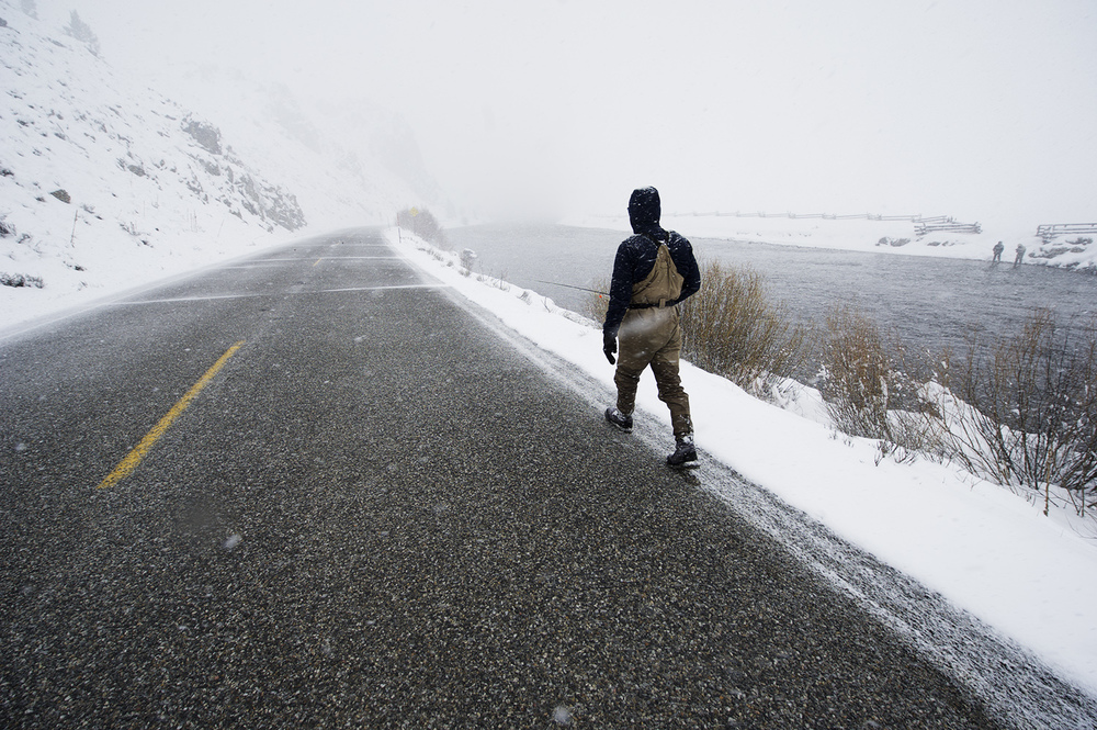 An angler takes a casual stroll down the highway to get to the Salmon River during a late winter storm.
