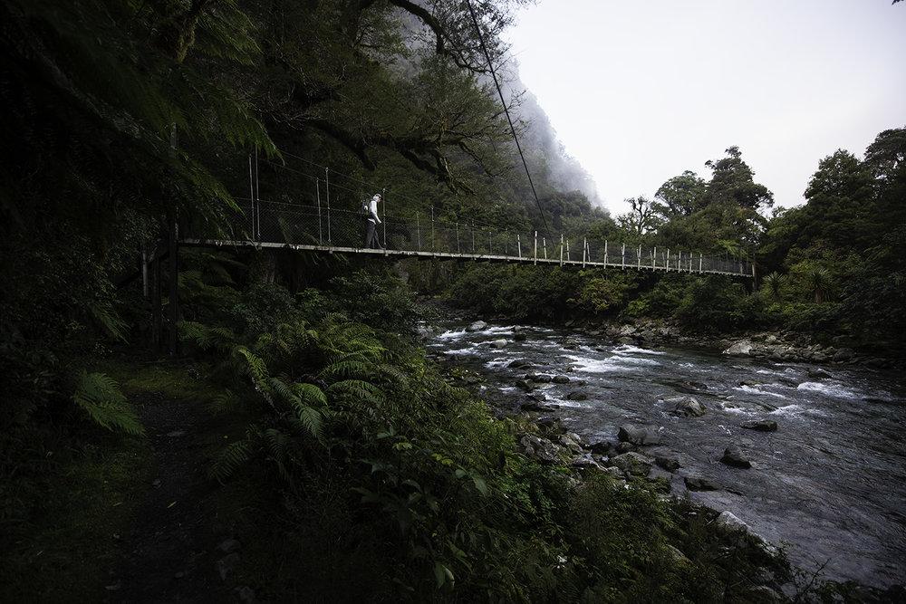 Will Price crosses a Fiordland river.