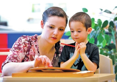 STAFF PHOTO JASON IVESTER Teacher Amy Chiodo helps Byrce Larson, 4, learn numbers on a clock Wednesday at the preschool at The Jones Center.