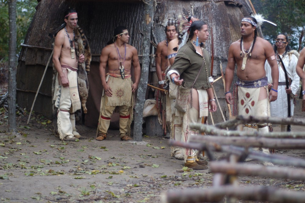 Wampanoag actor (Jonathan Perry, green shirt) portraying Tisquantum, speaking to Massasoit (played by Dave Weeden) in Desperate Crossing. Promotional image courtesy of Lone Wolf Documentary Group.