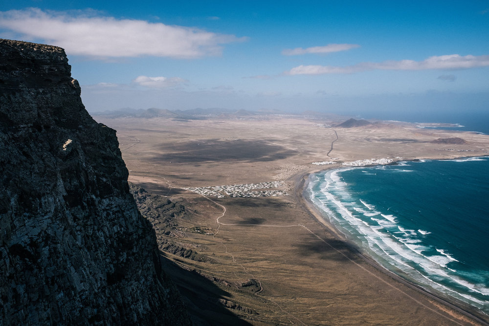 Caleta de Famara - The north of the Island, around Famara and Haría, is made up of amazing coastlines, gigantic cliffs, a few volcanoes, and even a desert. This Island manages to fit so many landscapes into such a small area!