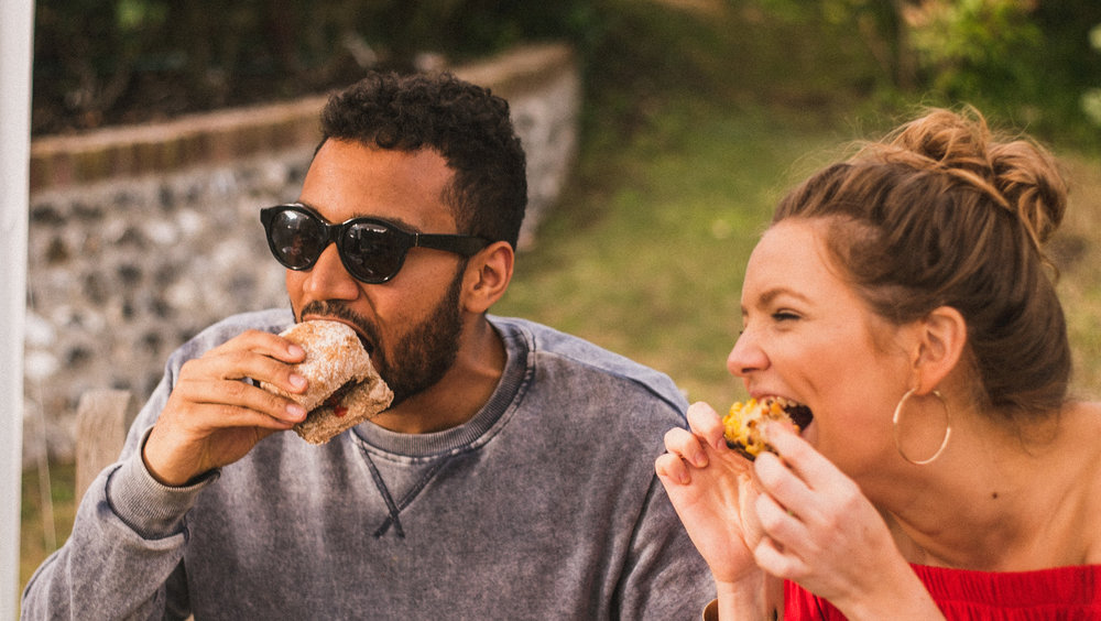 Couple eat hamburgers birling gap, Sussex