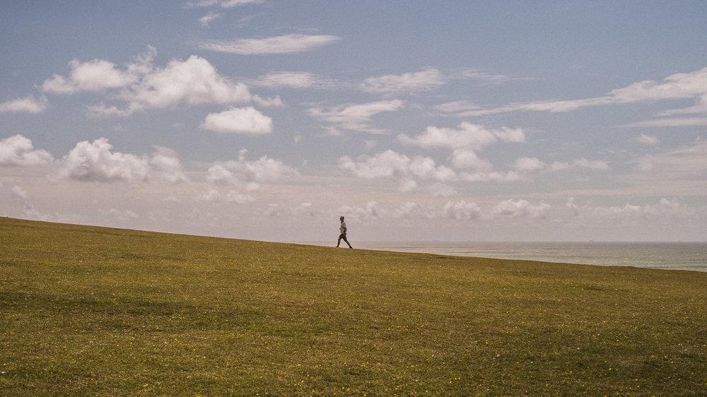 Man walks along a cliff birling gap, Sussex