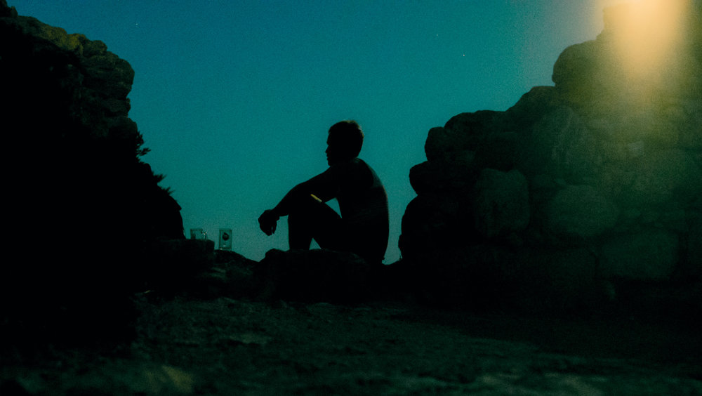 Shiloette of man drinking in Loutro, Crete